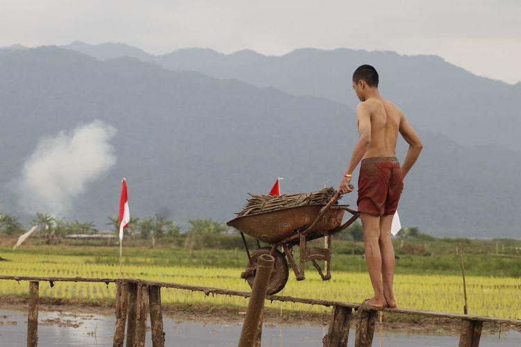 Man carrying firewood in wheelbarrow on narrow footbridge
