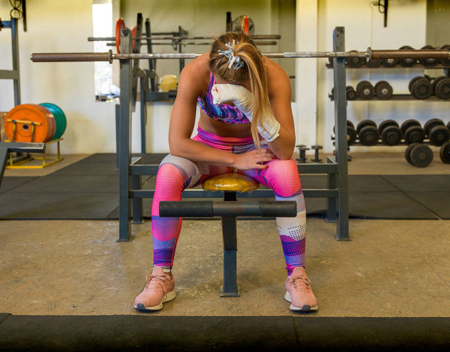 Tired woman with injured hand sitting at gym