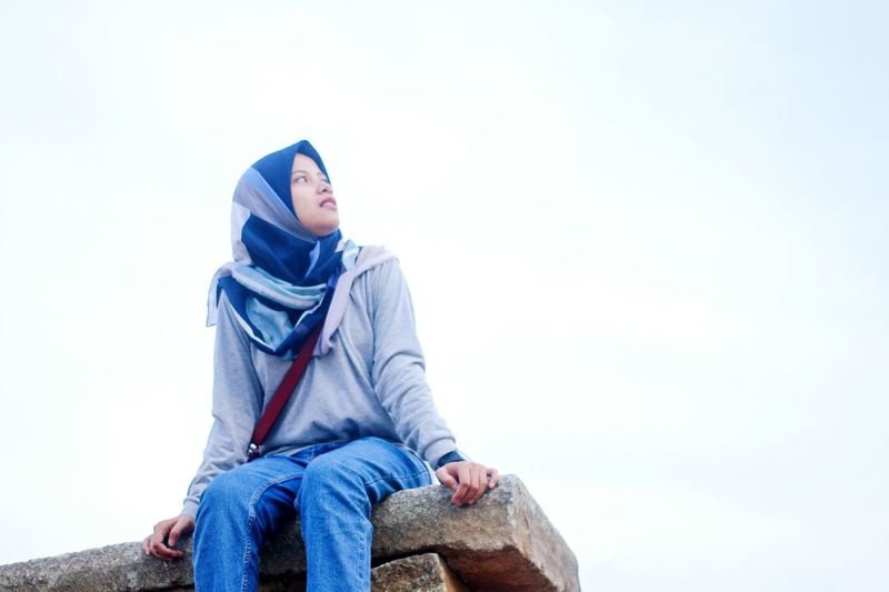 Low angle view of woman looking away against clear sky