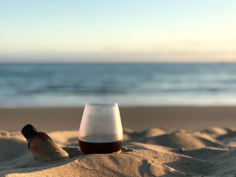 Sunrise Cold Drip Black Coffee Coffee Beach Water Sea Land Sky Sand Focus On Foreground Nature Sunlight No People Beauty In Nature Scenics - Nature Close-up Tranquil Scene Horizon Over Water Bottle Outdoors