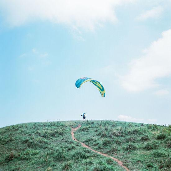 Kite flying over grassy field against sky