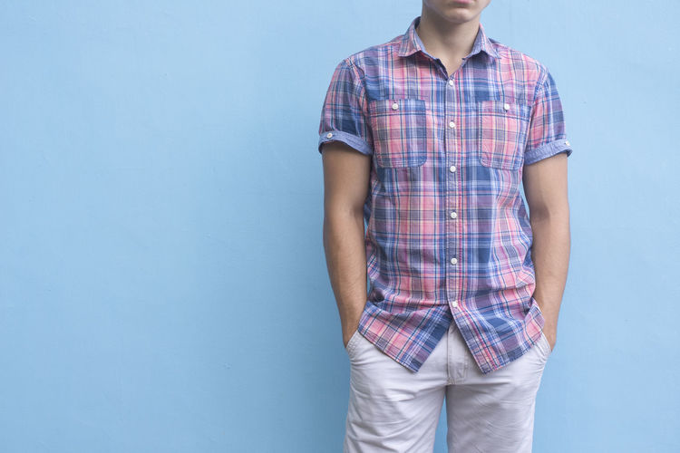 Young man on blue wall - background Adult Casual Clothing Cool Crossed Day Fashion Male Manager Model One Animal One Person Portrait Shirt Smart Standing Standing Studio Shot Success Young Young Adult