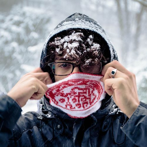 Portrait of man covering face with mask during winter