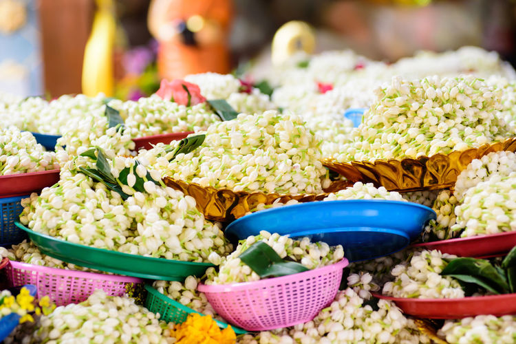 Close up hand of Golden buddha statue in the temple Chiangmai Thai Thailand ASIA Asian  Basket Belief Faith Flora Floral Flower Garland Heap Jasmine Offering Pile Pray Praying Respect Success Temple Tray Worship