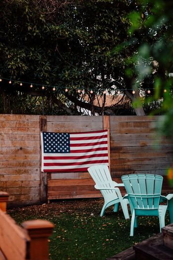 Absence Adirondack Chairs American Flag Architecture Backyard Bistro Lights Built Structure Day Empty Grass Growth Nature No People Outdoors Patriotic Patriotism Red Tranquility Tree Wood - Material Wooden