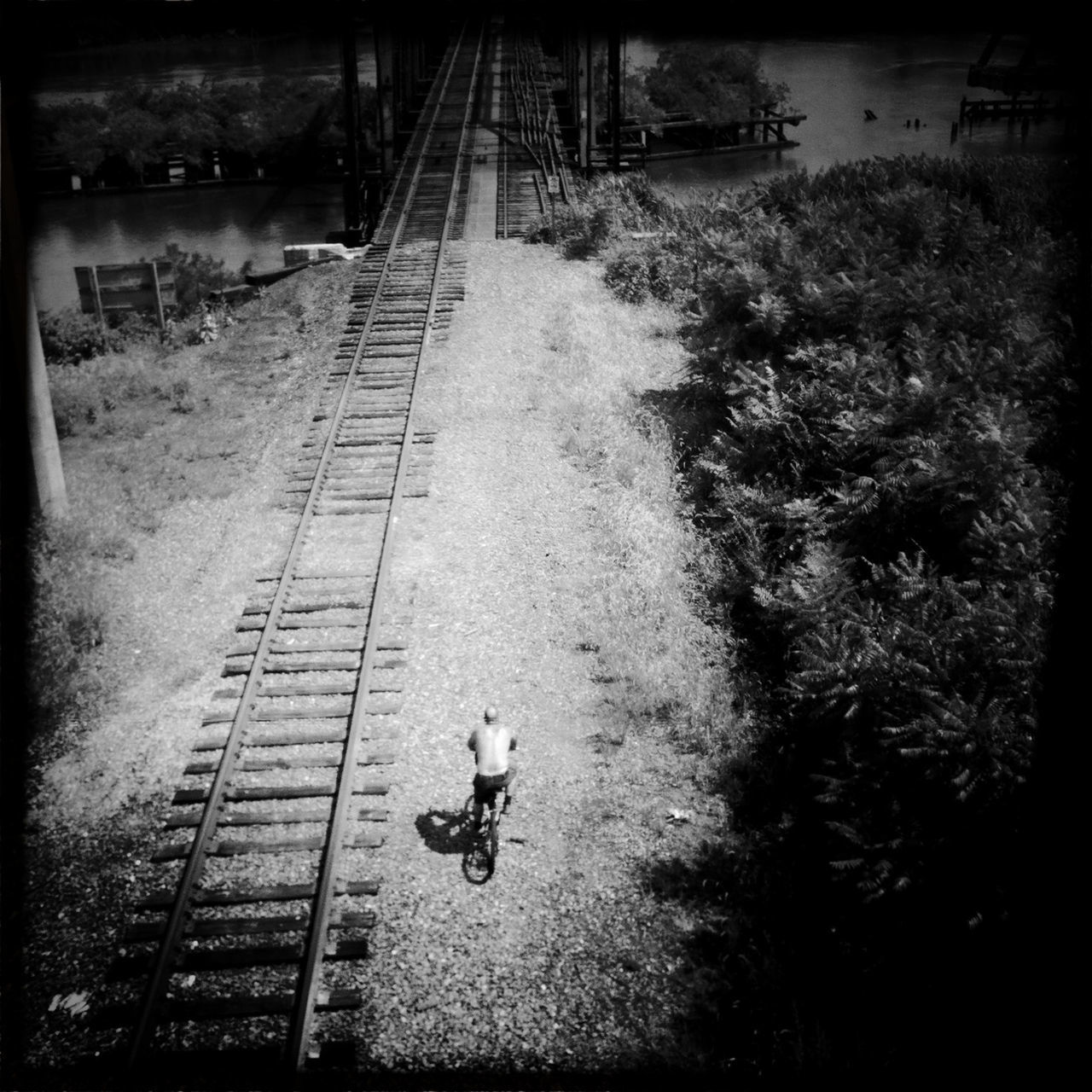 High angle view of shirtless man cycling by railroad tracks