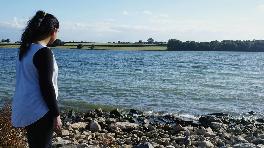 Girl At Lake Rocks Rocks And Water Landscape Enjoying Life Thinking About Life Staring At The Sea Water Lake Rutland Water Trees Fields Chilly Sunlight Reflection Duck Crashing Waves  Finding New Frontiers