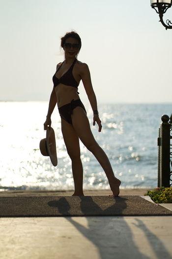 Full length portrait of woman in bikini standing at beach