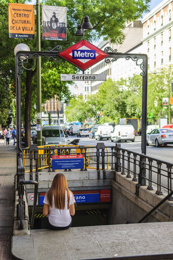 A young woman sitting on the steps of the Serrano Metro exit in Goya street in Madrid. Building Exterior Editorial  Exit Metro Metro Station One Person Outdoors Public Transportation Serrano Sign Sitting Streetphotography Text Tourism Transportation Travel Young Adult Young Women