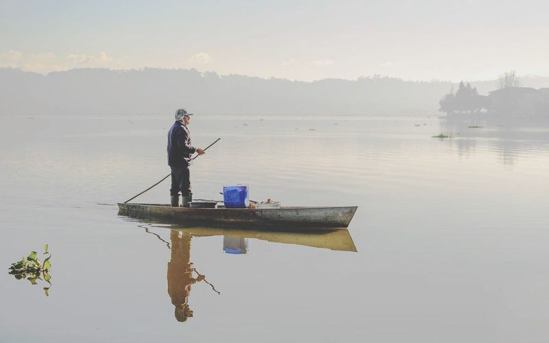 Man fishing in lake against clear sky