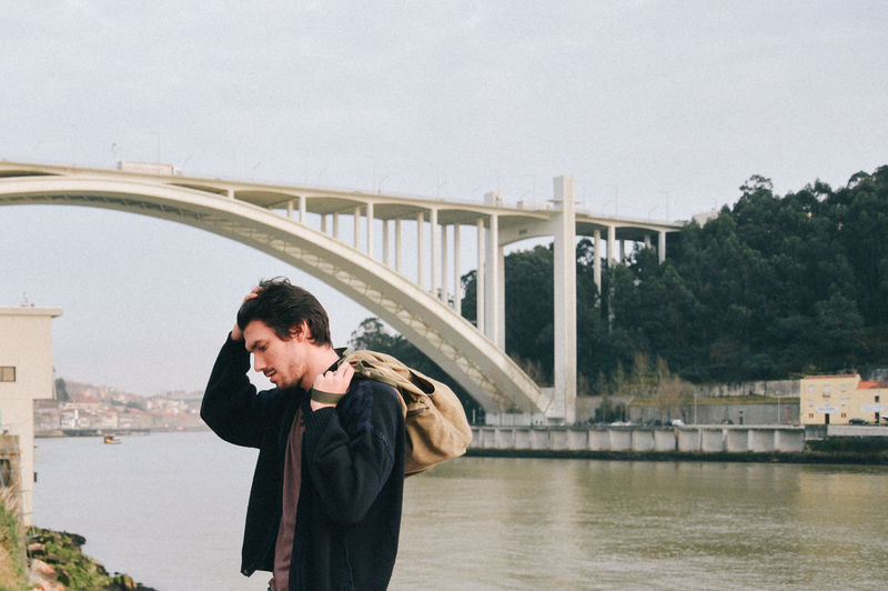 Thoughtful man looking away while standing against bridge