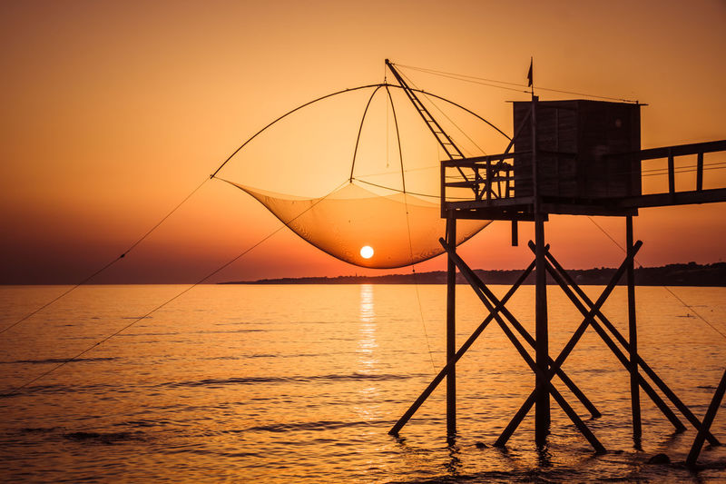 Water Sunset Sky Sea Scenics - Nature Orange Color Beauty In Nature Horizon Over Water Waterfront Horizon Tranquility Tranquil Scene Fishing Net Nature Architecture Fishing Silhouette Built Structure Reflection Sun No People Fishing Industry Outdoors Fishing Hut Fishing Net