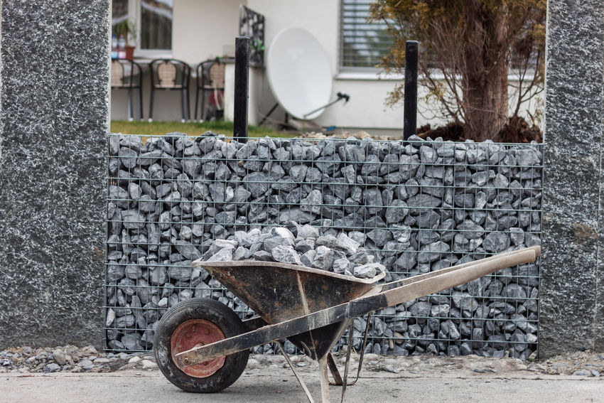 wheelbarrow full with gravel Construction Construction Site Wheelbarrow Architecture Building Exterior Gabion Gabion Wall Garden Design Gravel Horticulture No People Work Tool