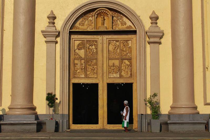 Full length of senior man in front of door