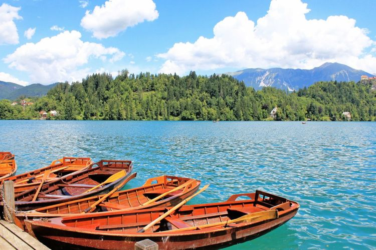 Boats in lake with mountain range in background
