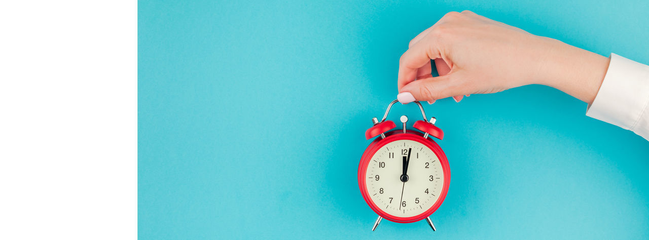 Close-up of woman with alarm clock against blue background
