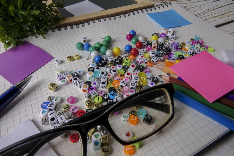 High angle view of alphabet beads with school supplies on table