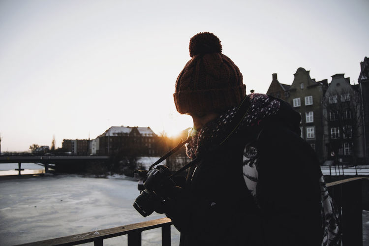 Man Using Camera While Standing In City During Winter