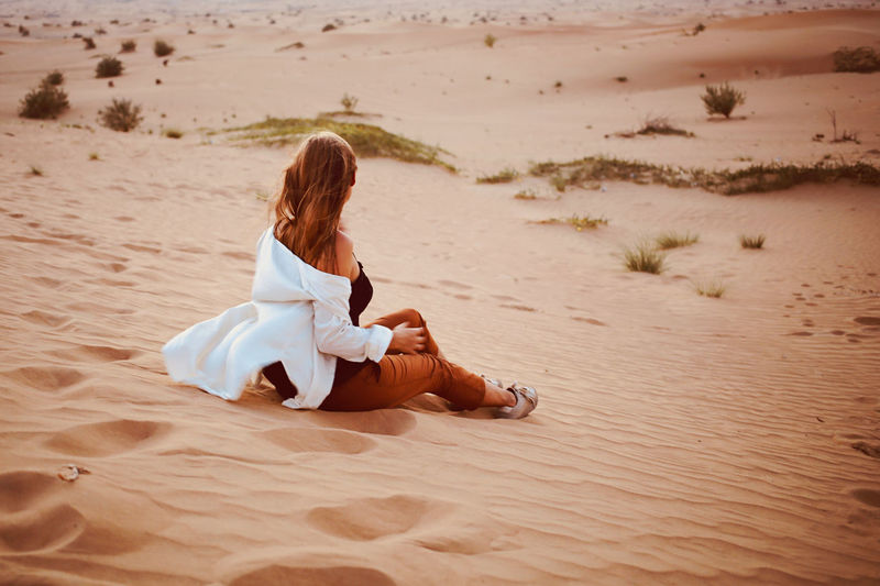 Woman sit back at desert sand