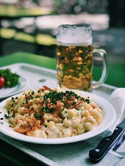 Close-up of pasta served with beer on table