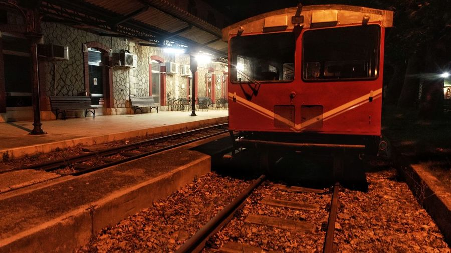 Train at railroad station platform at night