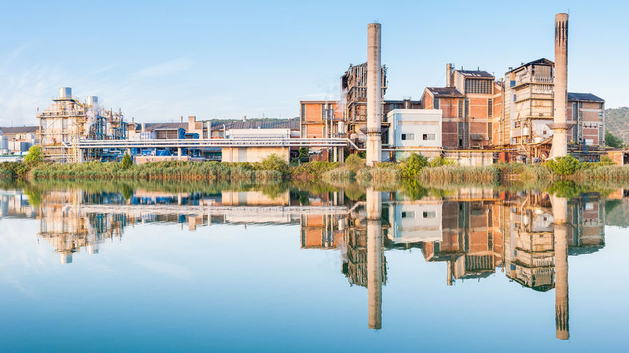 Reflection of industrial buildings on lake