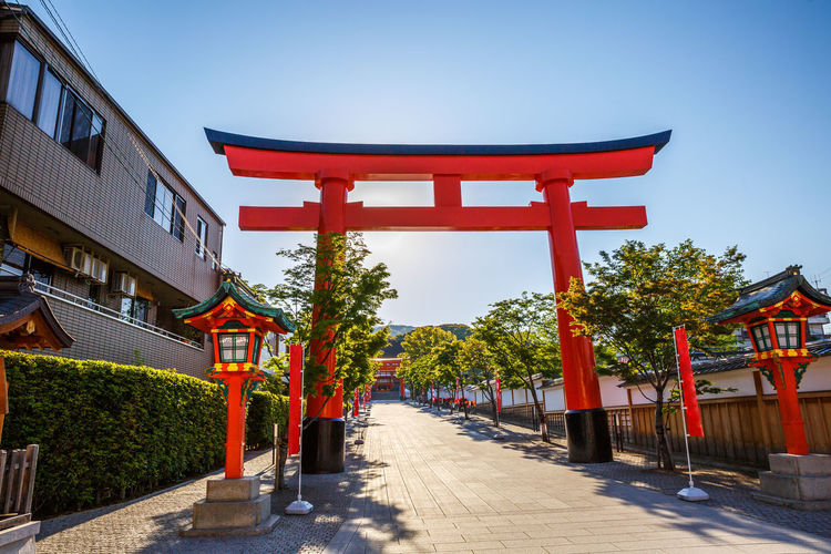 Kyoto, Japan - April 28, 2017: tourist woman walking under red torii gates of famous landmark Fushimi Inari shrine. Travel asia concept. Kyoto's popular landmark. Kyoto, Japan - April 28, 2017: Fushimi Inari Taisha is the most important Shinto shrine famous for its thousands of red torii gates.The lettering engraved on pole are the name of donated organizations Fushimi Fushimi Inari Taisha Fushimi Inari Taisha Shrine Gates Japan Photography Kyoto, Japan Shinto Shrine Shinto Temple TORII Torii Gate Tourist Tourist Attraction  Woman Architecture Belief Building Building Exterior Built Structure Clear Sky Direction Footpath Fushimi Inari Kyoto Fushimi Inari Shrine Japan Culture Kyoto Kyoto Japan Kyoto,japan Kyotojapan Nature No People Outdoors Place Of Worship Plant Religion Shinto Of Japan Shintoism Shrine Sky Spirituality The Way Forward Torii Gate Japan Travel Destinations Tree