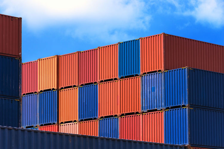 Stack of multi colored cargo container at harbor against blue sky