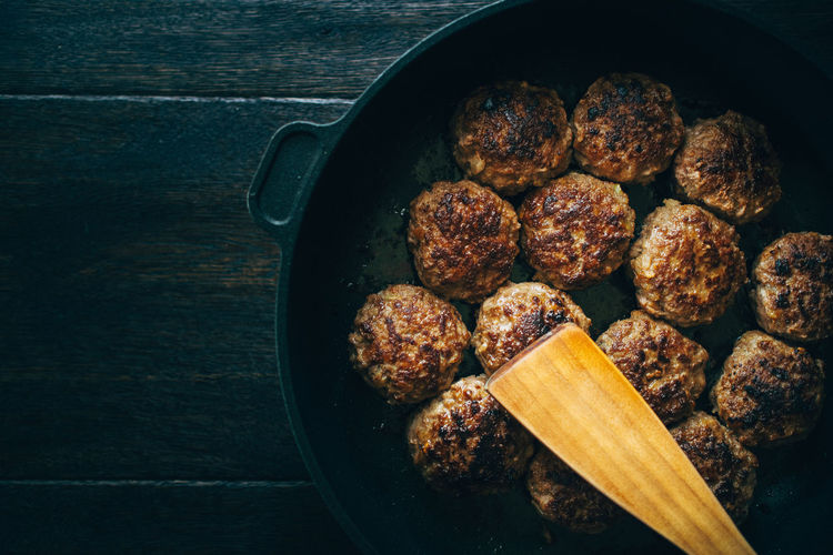 Spatula with meatballs in cooking pan