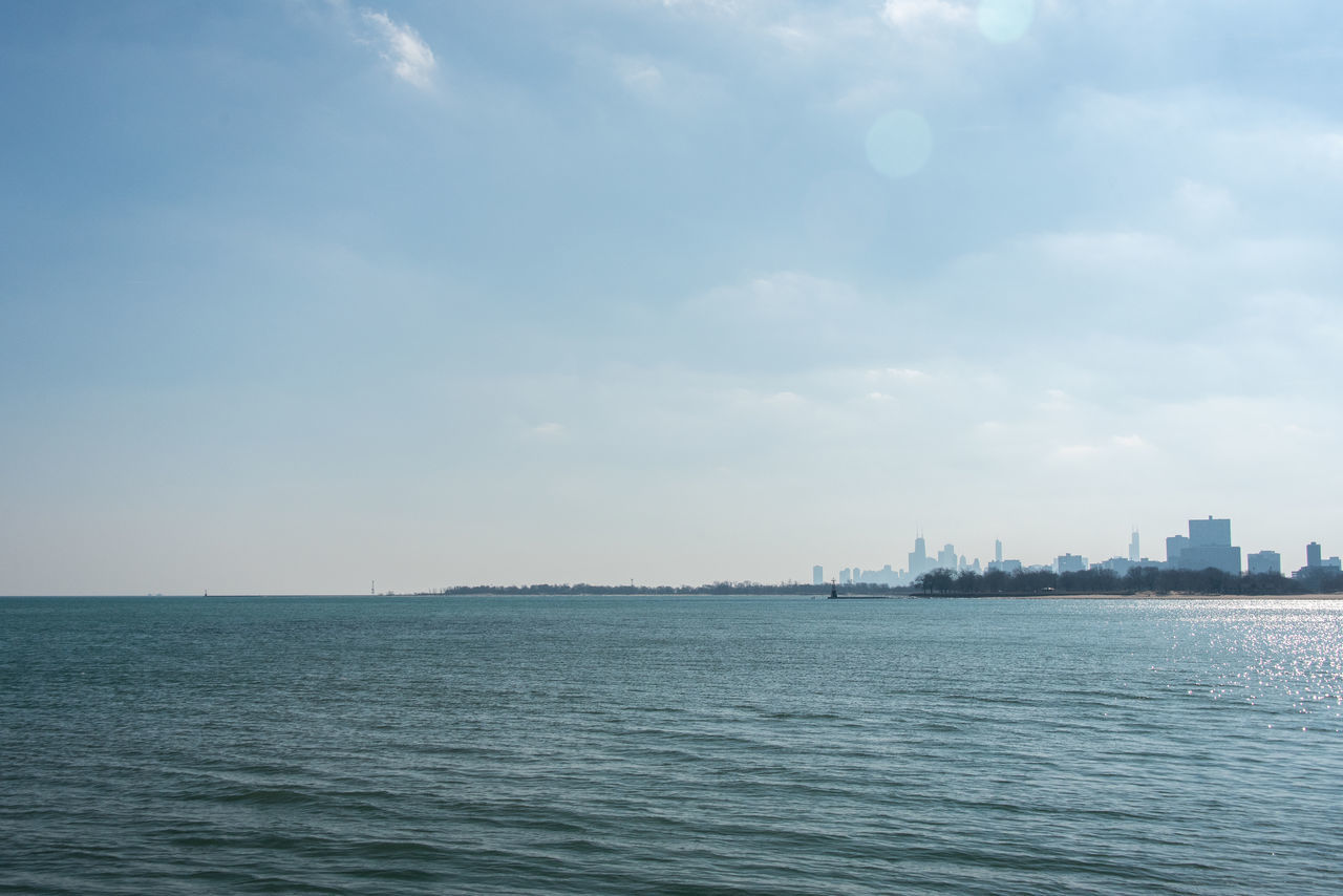 waterfront, sea, sky, water, skyscraper, cityscape, outdoors, no people, building exterior, cloud - sky, city, architecture, travel destinations, scenics, rippled, day, nature, urban skyline, tranquility, built structure, beauty in nature, horizon over water