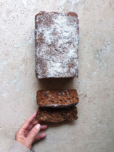 Hand holding slice of date and walnut loaf cake on stone table
