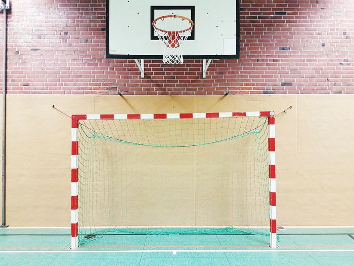 Low angle view of basketball hoop against wall in gym