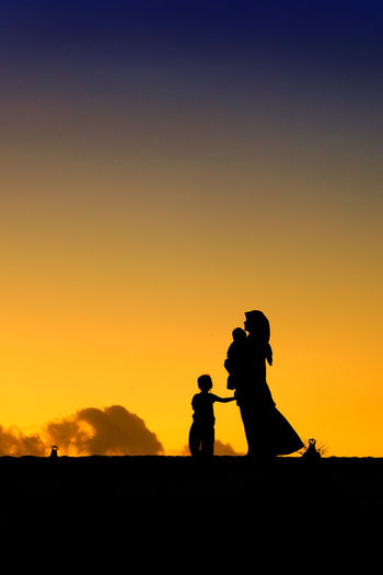 Silhouette of woman with children at sunset