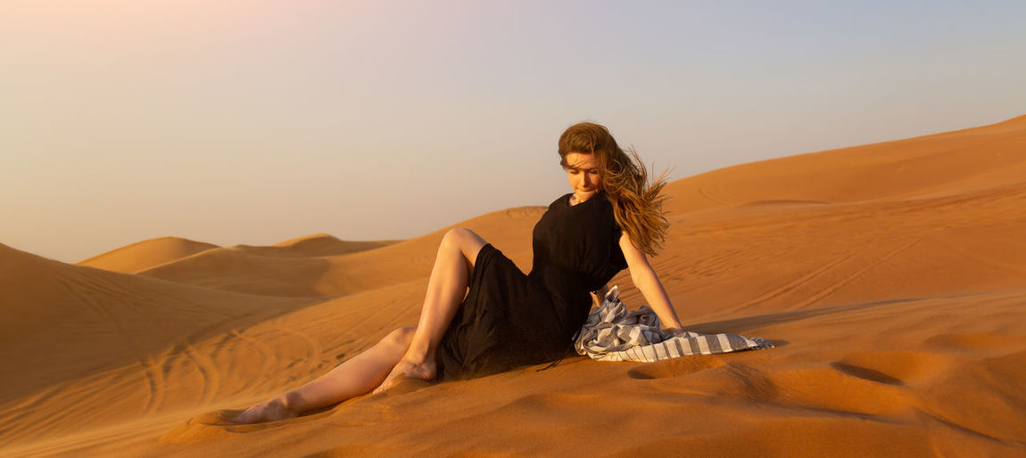 Young woman in desert against sky