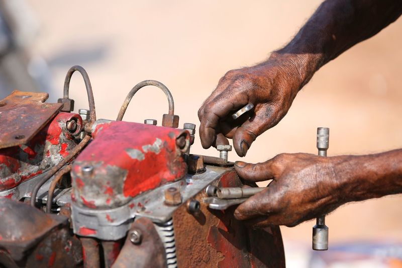 Close-up of man hands working on rusty machinery