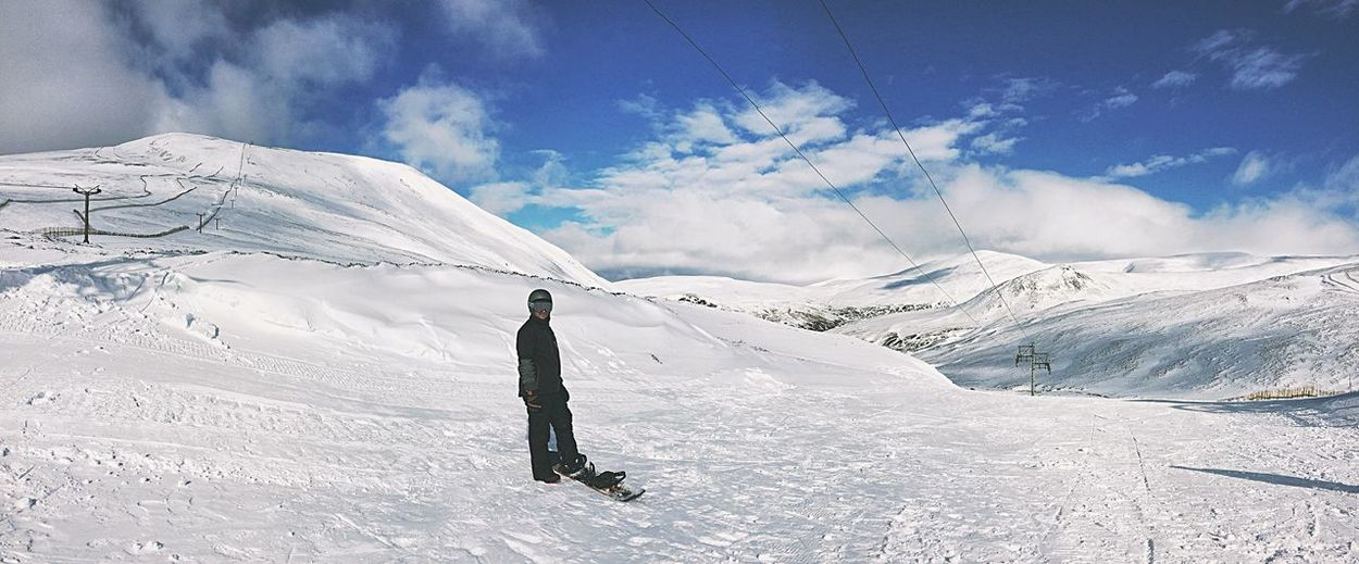 Man standing with snowboard on snowcapped mountain against sky