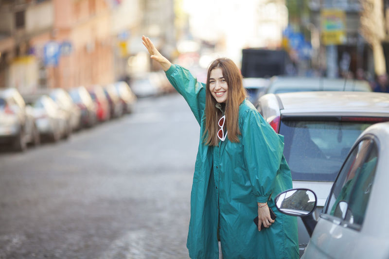 Portrait of smiling woman gesturing while standing by cars on street in city