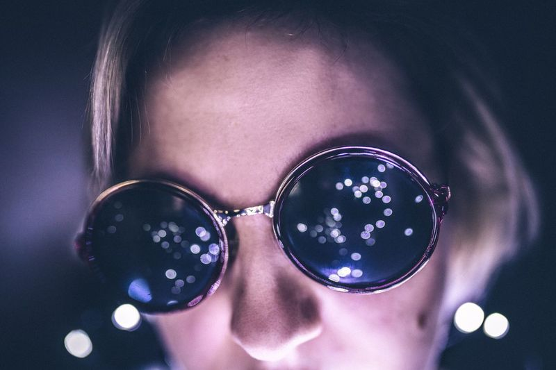 Close-up of young woman wearing sunglasses in illuminated room