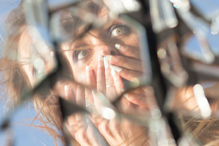 Close-Up Of Mid Adult Woman With Hands Covering Mouth Reflecting On Broken Glass