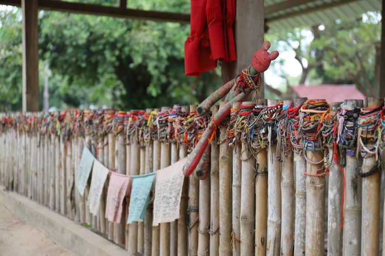 Prayer flags hanging against wooden fence