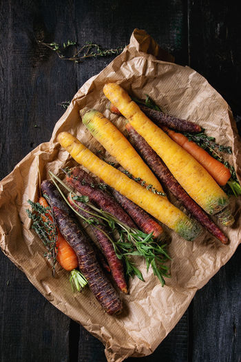 Heap of colorful raw carrots with fresh thyme herbs on paper bag over black wooden surface. Top view. Herbs Assortment Carrots Colorful Vegetables Colorful Veggies Dark Background Directly Above Food Food And Drink Freshness Healthy Eating Healthy Food Raw Food Raw Vegetables Snack Table Top View Uncooked Variety Vegetable Wood - Material Wooden Texture Yellow Carrots