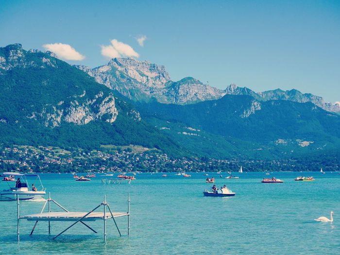 People boating in lake annecy against mountains on sunny day