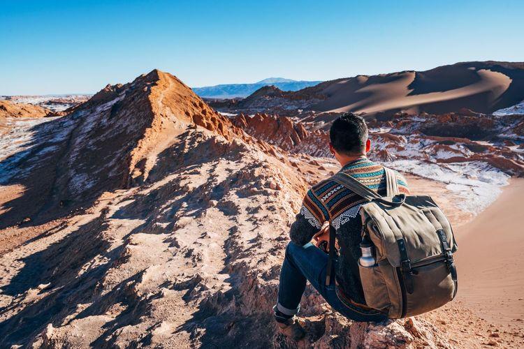 Rear view of man sitting on rock formation at valle de la luna