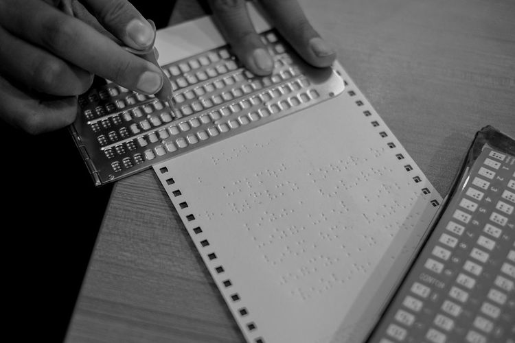 High angle view of person preparing braille book