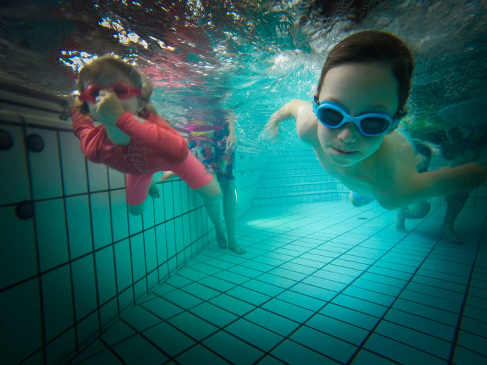 A boy and a girl swimming underwater in a pool