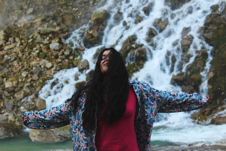 Young Woman Standing With Arms Outstretched Against Waterfall
