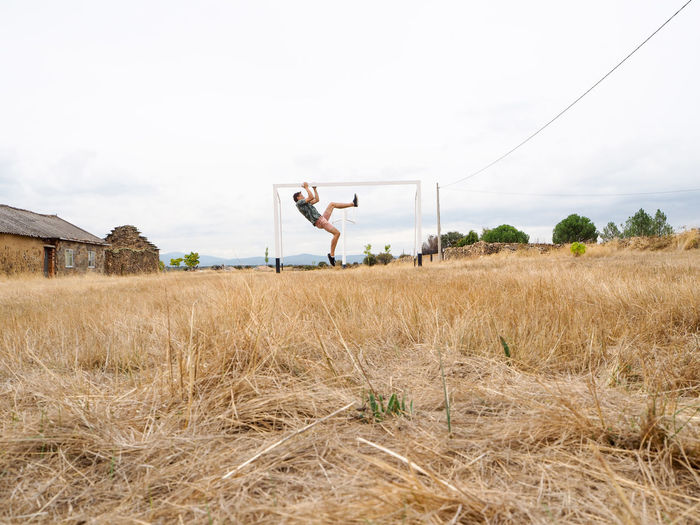 Man hanging from soccer goal on grassy field against sky