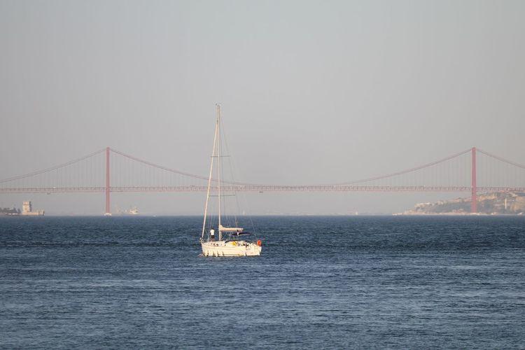 Yacht Over Tagus River Against 25 De Abril Bridge