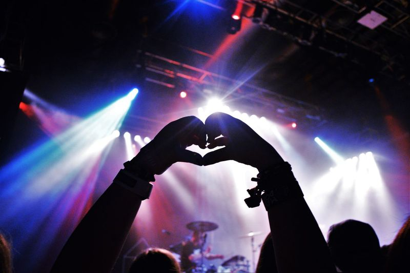 Cropped silhouette hands making heart shape at music concert