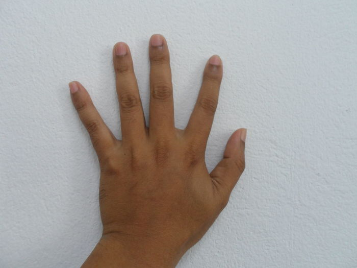 Cropped hand touching against wall